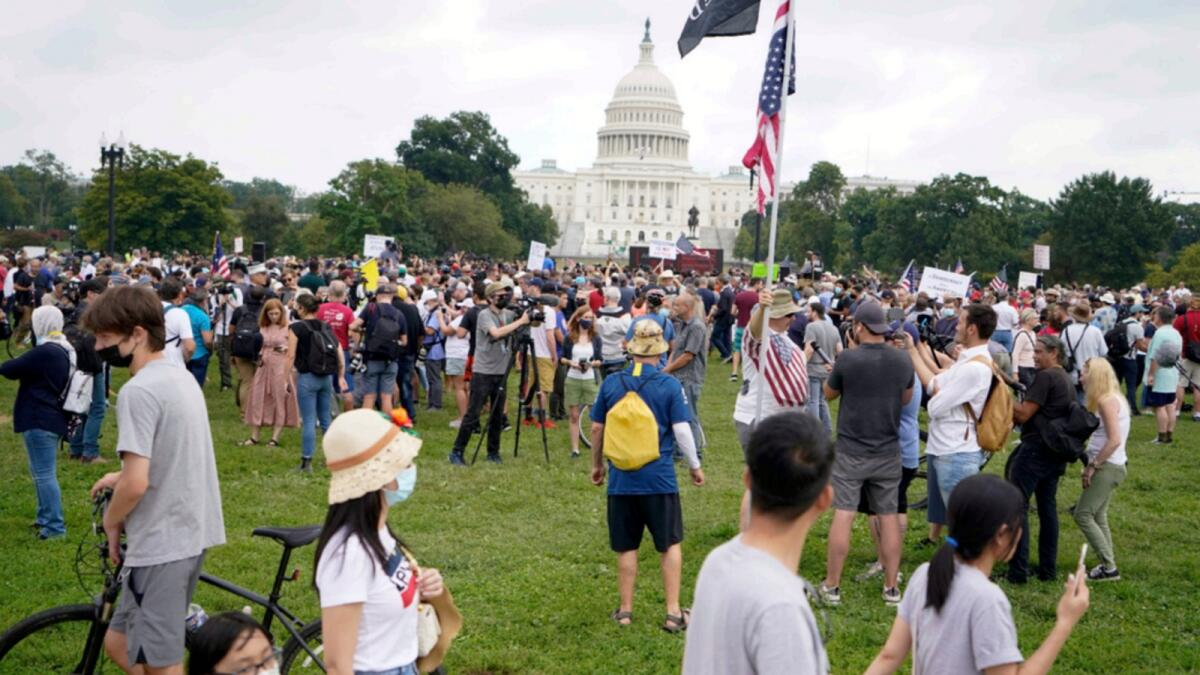 People walk by as others attend a rally near the US Capitol in Washington. — AP