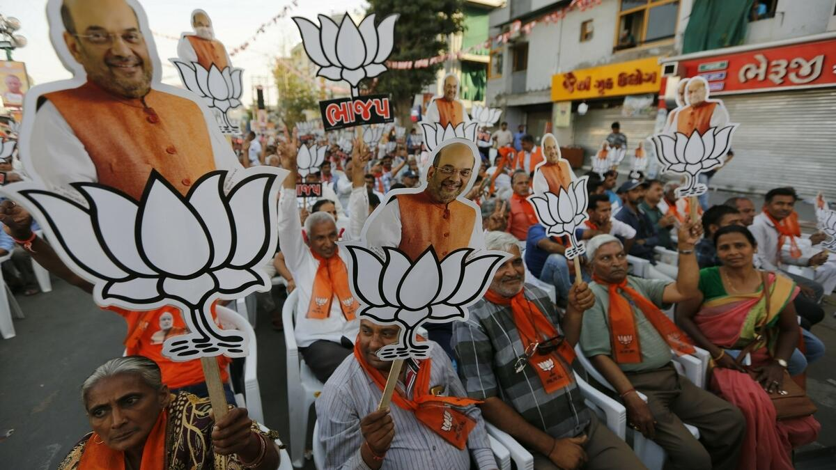 Supporters of Indias ruling Bharatiya Janata Party (BJP) hold cutouts of party president Amit Shah with the party symbol during a public rally in Ahmadabad, India.-AP