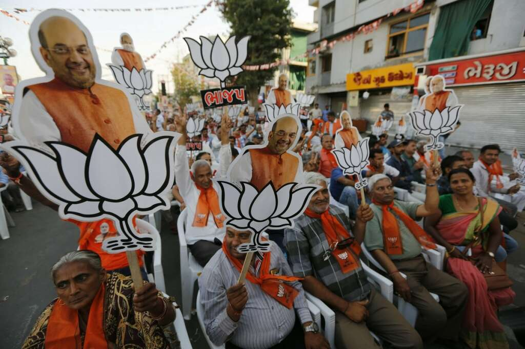Supporters of India's ruling Bharatiya Janata Party (BJP) hold cutouts of party president Amit Shah with the party symbol during a public rally in Ahmadabad, India.-AP