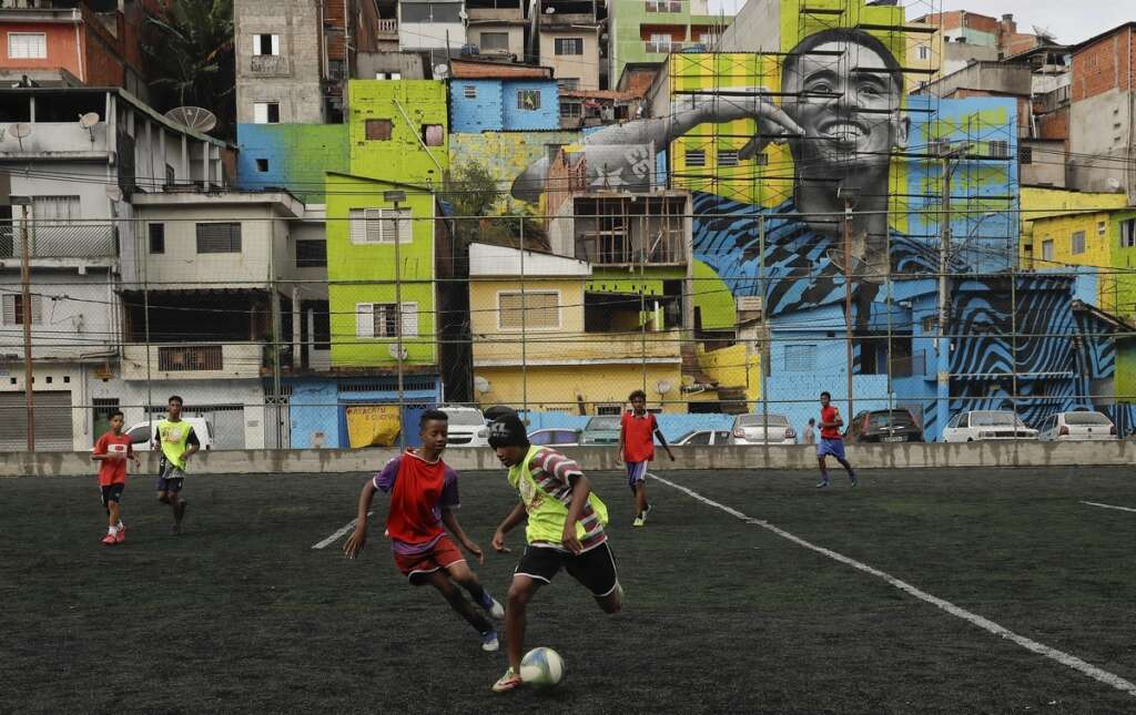 01f79c6e955 Kids play in the Jardim Peri neighbourhood where Manchester City s  Brazilian star Gabriel Jesus grew up and is featured in a mural on the side  of homes in ...
