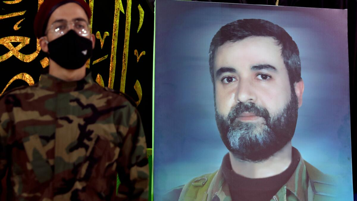 A Hezbollah fighter stands next to a picture of Ali Atwa in the southern Beirut suburb of Dahiyeh. Photo: AFP