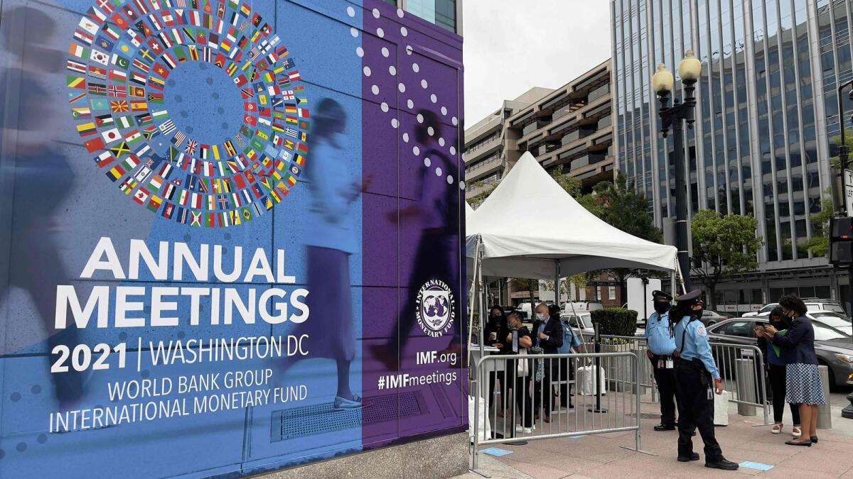 People wait outside the entrance to the annual meetings of The World Bank and International Monetary Fund (IMF) outside the IMF headquarters in Washington. The annual meetings are running from October 11-17, 2021. — AFP