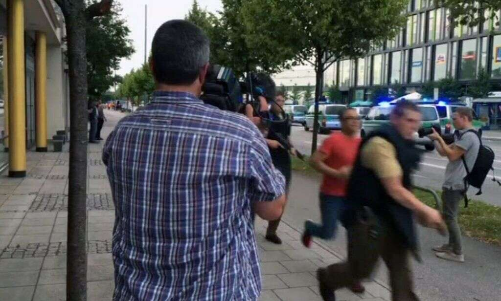 Armed police move past on looking media responding to a shooting at a shopping center in Munich, Germany