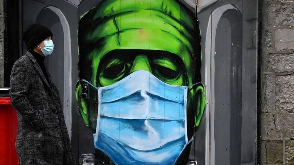 A man walks past a graffiti of a Frankenstein wearing a protective face mask on a doorway amid the spread of the Covid-19 pandemic, in Galway, Ireland. — Reuters file