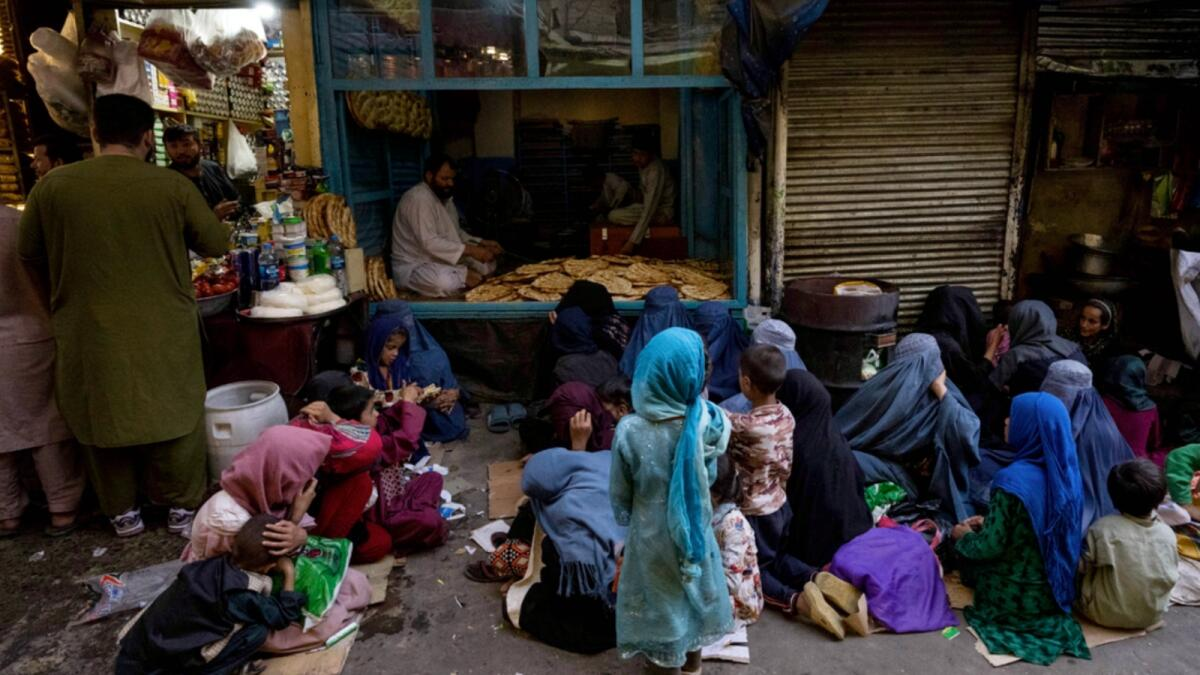 Afghan women and children sit in front of a bakery waiting for bread donations in Kabul's Old City. — AP