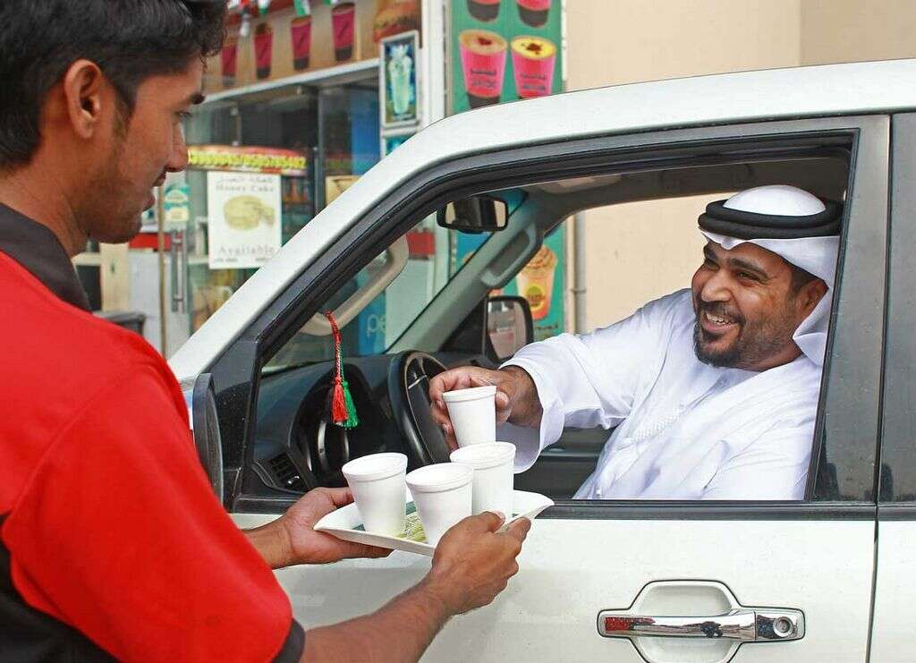 It's common to see Emiratis stop their cars outside  bsmall cafeterias as waiters serve them karak tea.