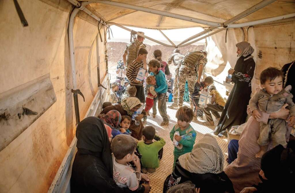 Syrian refugees receive water and food packets after arriving in Jordan. The UAE Cabinet announced on Monday that nationals of countries struck with war or natural disasters will be granted a one-year visa despite their current legal status.