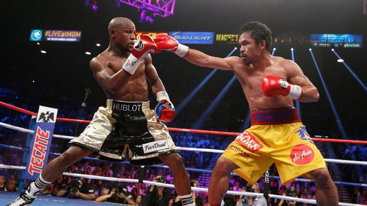 Floyd Mayweather Jr. (left) exchanges punches with Manny Pacquiao during their welterweight unification championship bout at MGM Grand Garden Arena in Las Vegas, Nevada.  (AFP file)