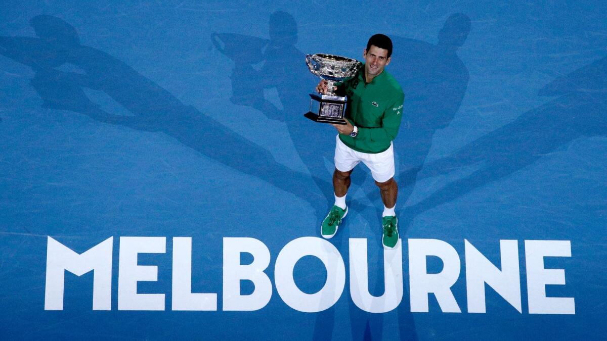 Serbia's Novak Djokovic holds the Australian Open trophy after defeating Austria's Dominic Thiem in the final last year. — AP file