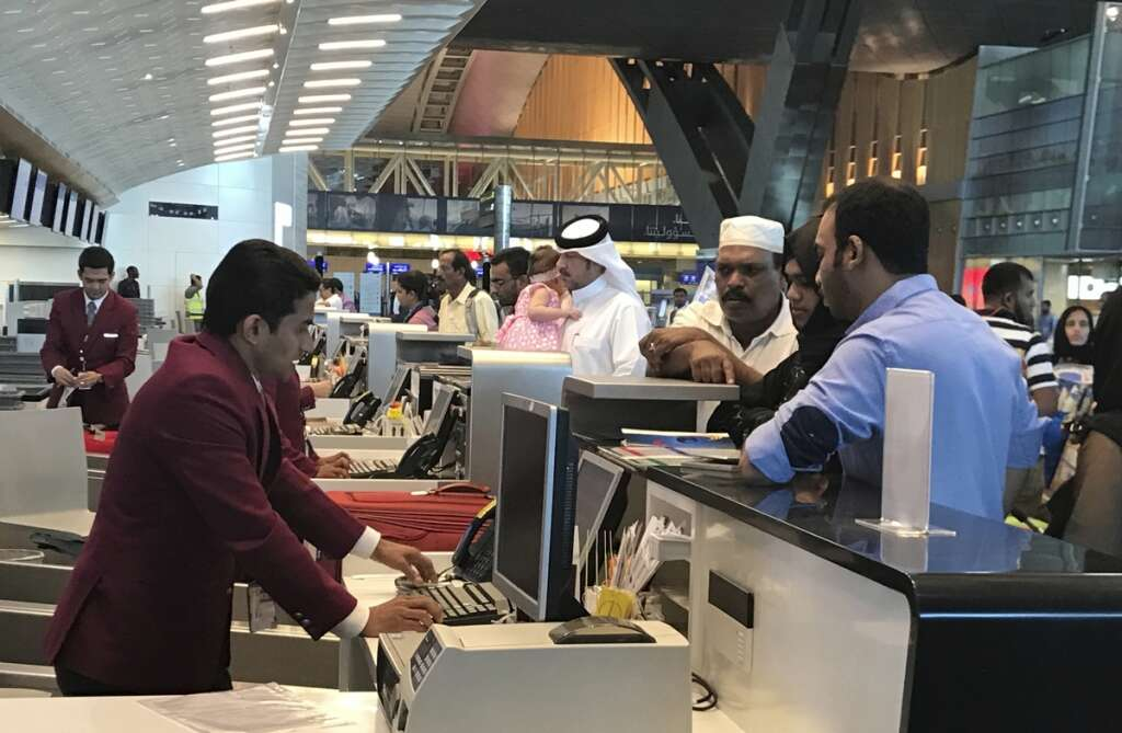 Qatari and other nationals queue at the check in counters of the Hamad International Airport in Doha, Qatar