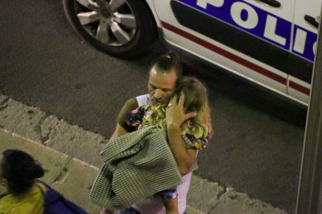 A man holds a child after a truck plowed through Bastille Day revelers in the French resort city of Nice, France,