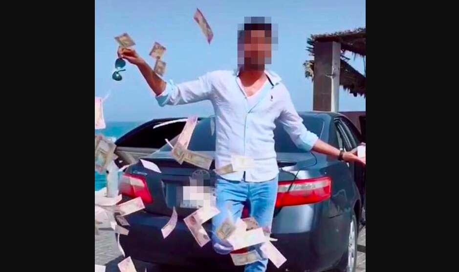 Asian man throws money in video shot in Dubai, arrested