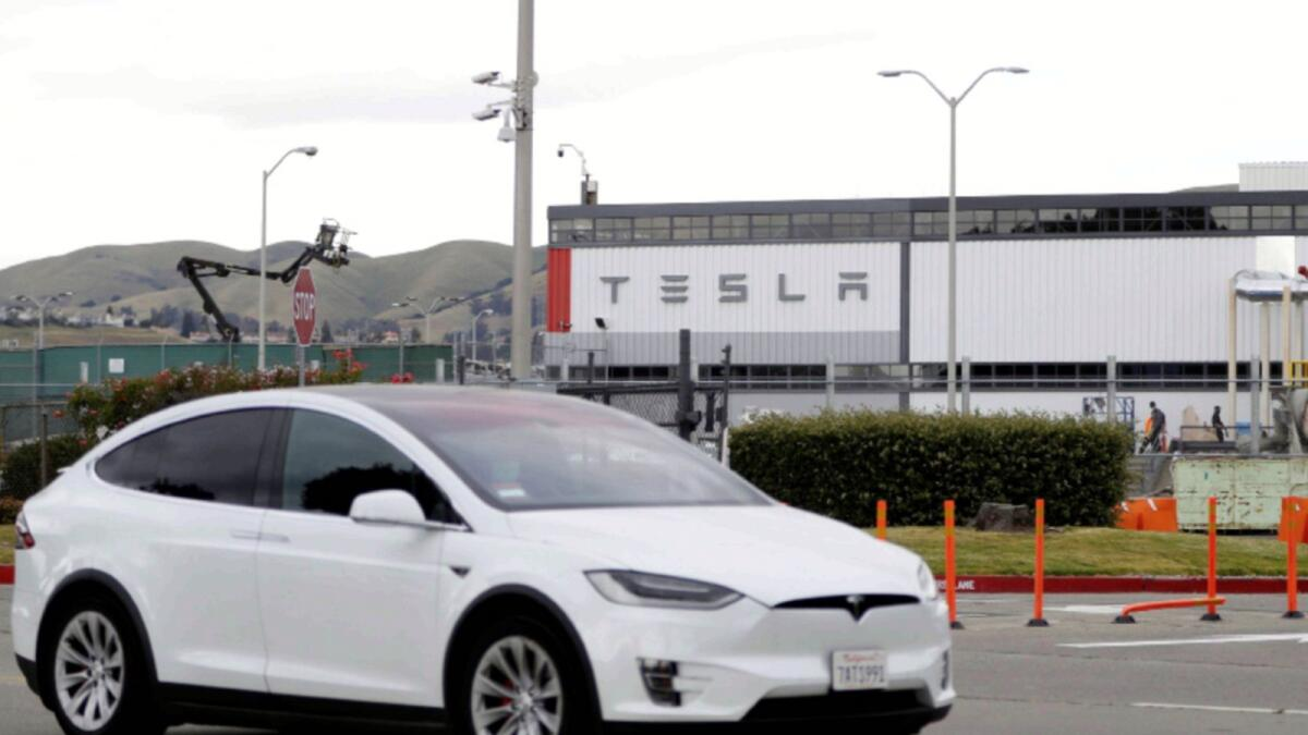 A Tesla vehicle drives past Tesla's primary vehicle factory in California. — Reuters file