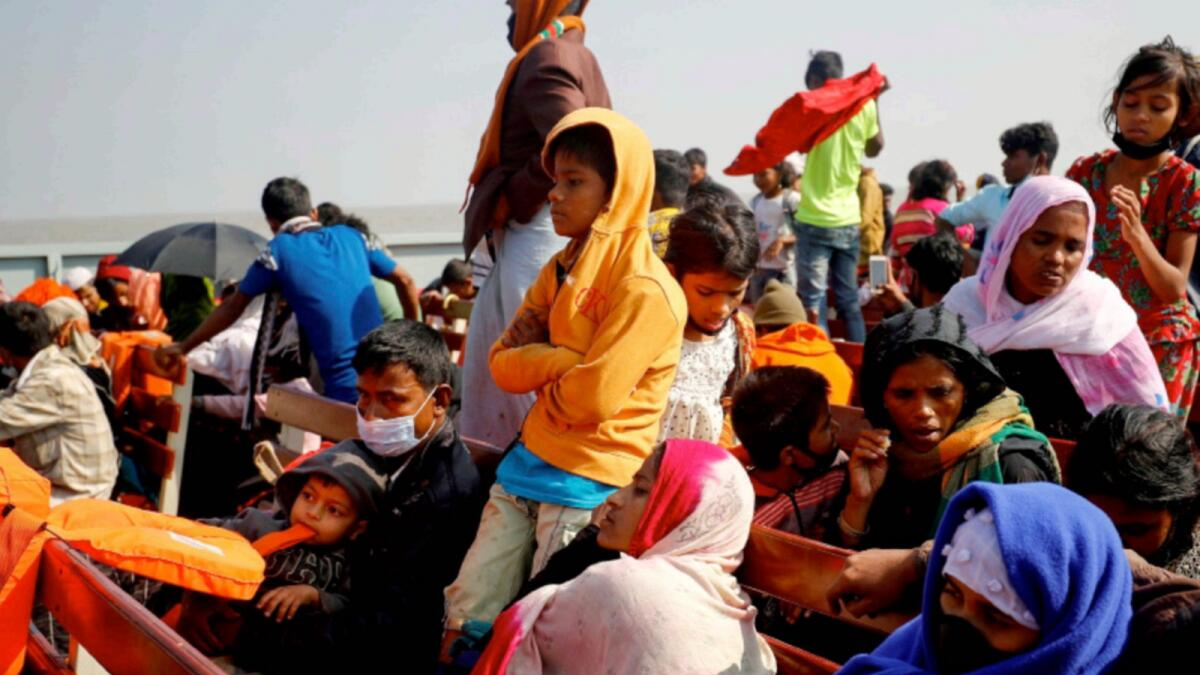 Rohingya refugees sit on wooden benches of a navy vessel on their way to the Bhasan Char island. — Reuters file