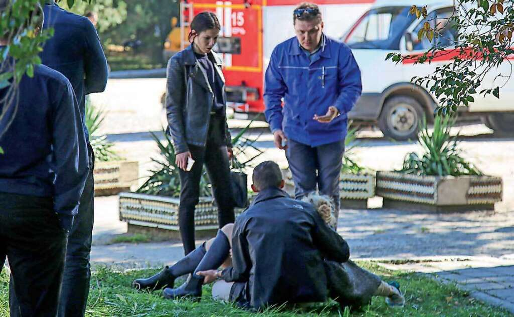 A rescuer carries an injured victim at the college in the city of Kerch on Wednesday. — AFP