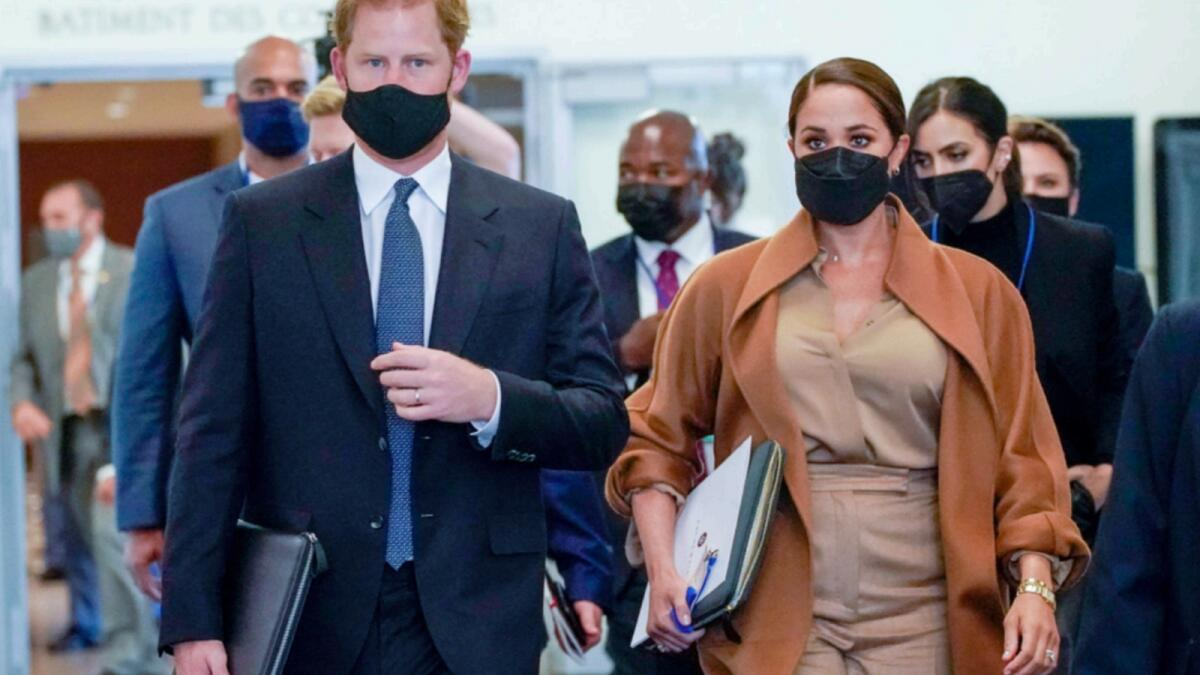 Prince Harry and Meghan are escorted as they leave the United Nations headquarters. — AP