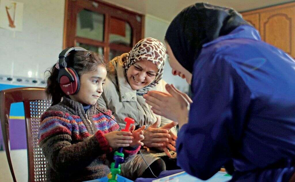 Syrian refugee Aya Al Souqi, left, smiles  during her first hearing test by Zaineb Abdulla, right, vice-president of  Deaf Planet Soul, a Chicago hearing charity, at Joub Jannine village in the Bekaa valley.