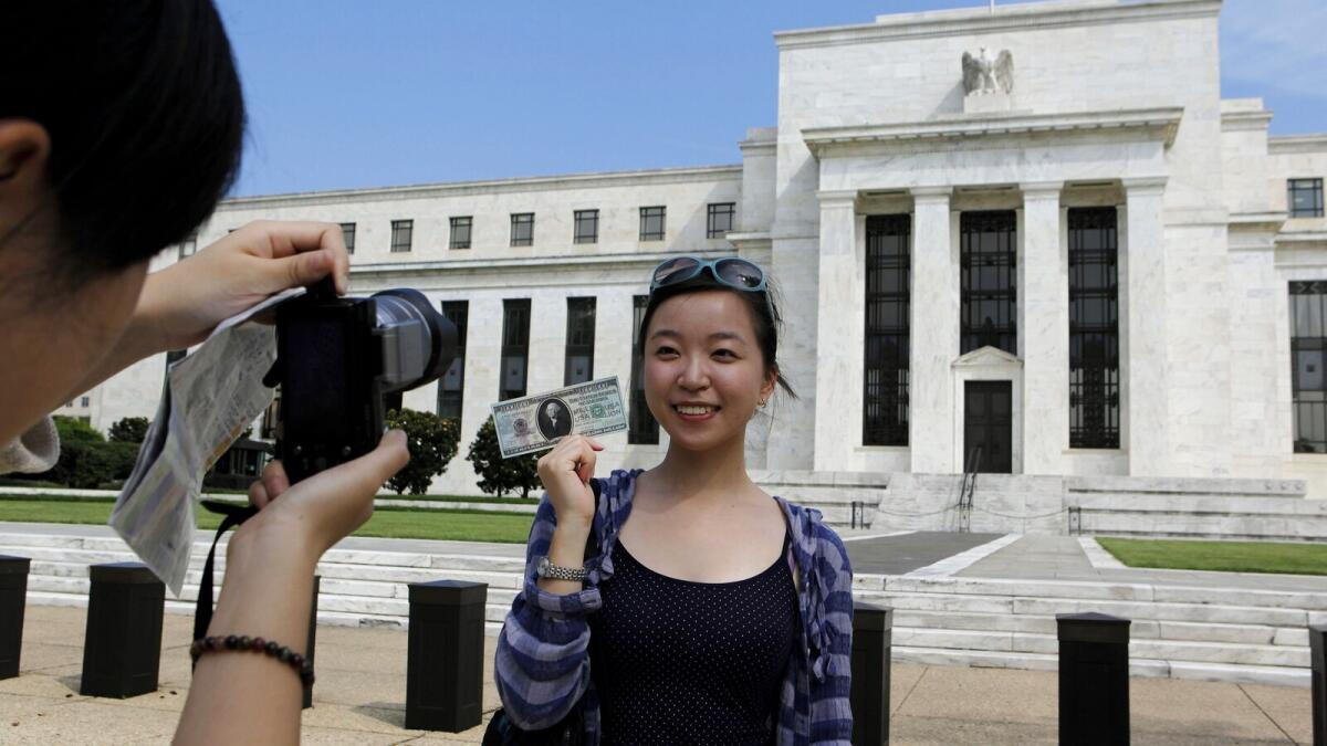 Chinese student Leyna Liu from Shanghai poses with a fake million dollar bill in front of the Federal Reserve building in Washington.