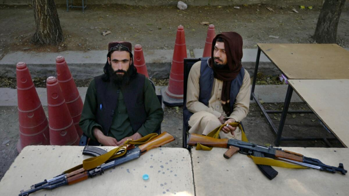 Taliban fighters sit outside the passport office after Taliban announced the reopening for passport applications, in Kabul. — AFP