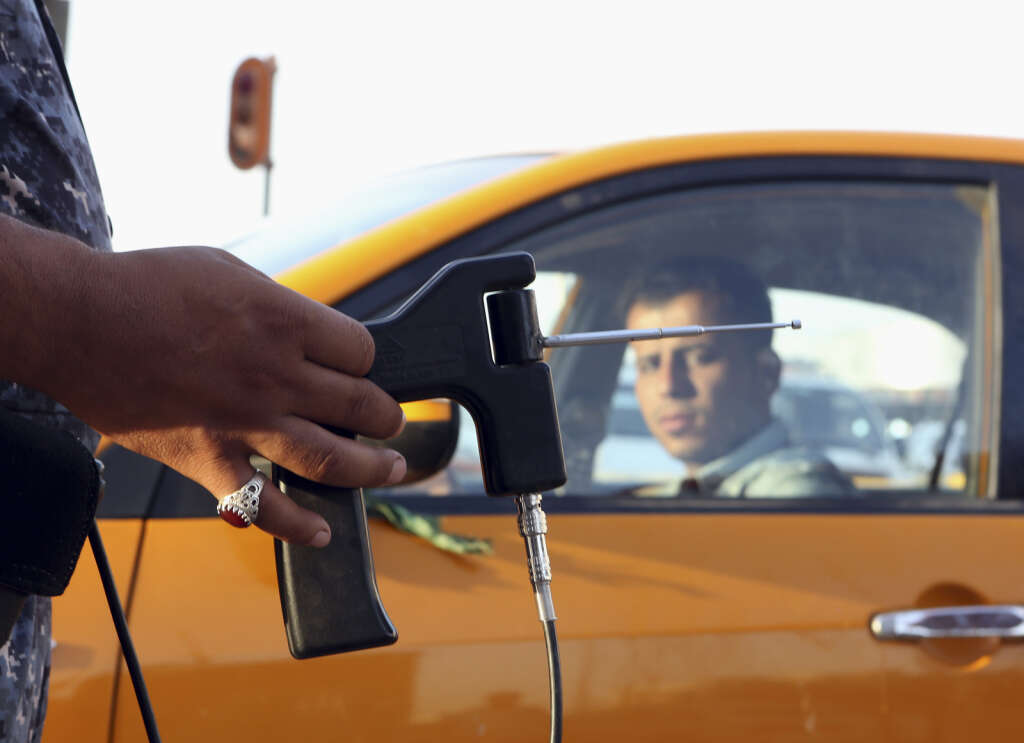 An Iraqi policeman uses a hand-held device that is supposed to detect bombs at a checkpoint in Basra.