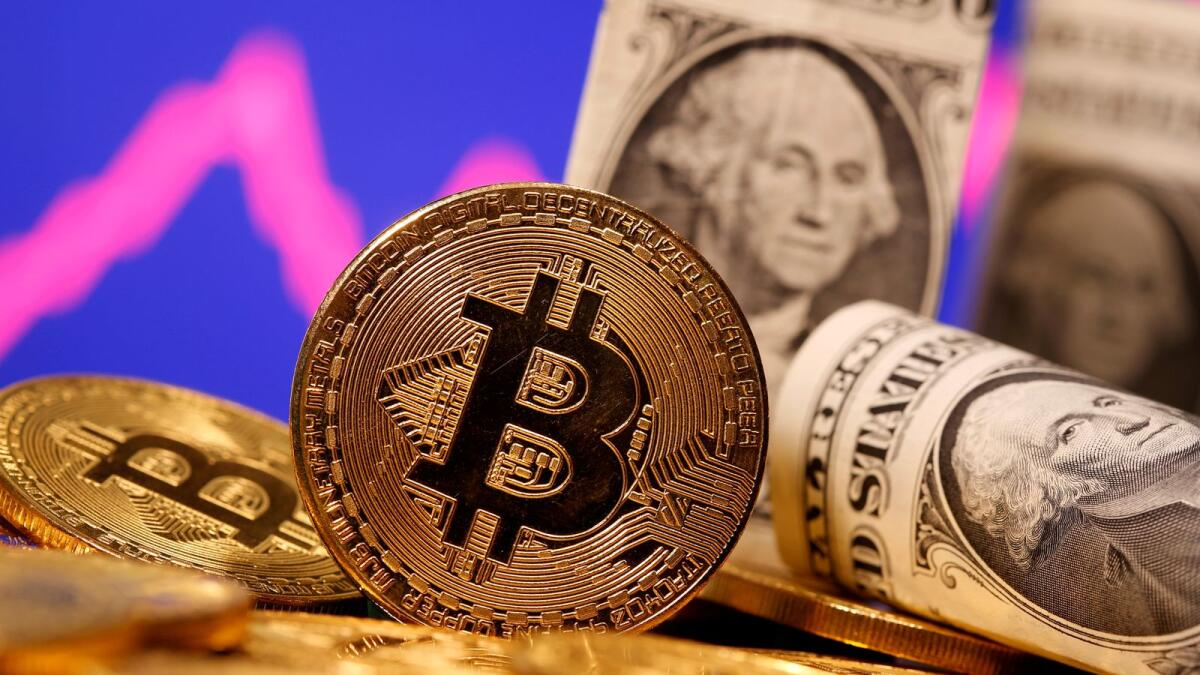 A representation of virtual currency Bitcoin and US one dollar banknotes are seen in front of a stock graph in this illustration. — Reuters file