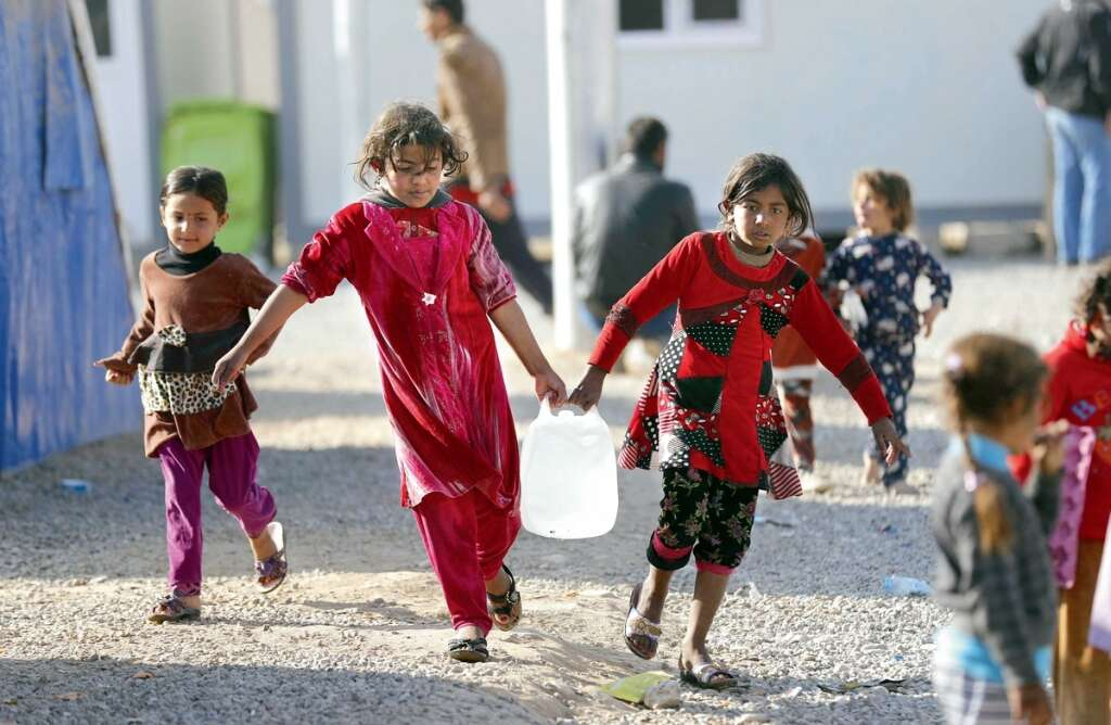 Iraqi children carrying jerrycans of water. The region is already facing a severe water crisis, and with temperatures expected to rise in coming years, the problem could get worse. — AFP file