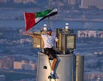 Shaikh Hamdan waves UAE flag from top of Burj Khalifa