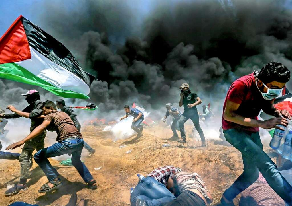 Palestinians run for cover from Israeli fire and teargas during a protest against the US embassy move to Occupied Jerusalem at the Israel-Gaza border on Monday. — Reuters