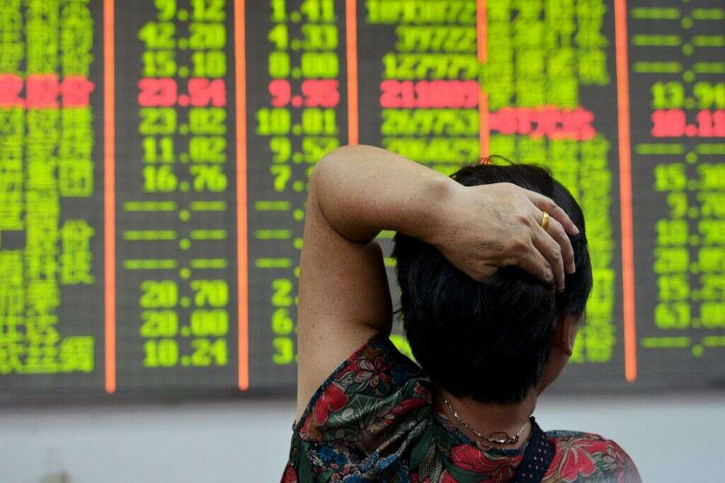 An investor looks at an electronic board showing stock information at a brokerage house in Hangzhou, Zhejiang province, China.