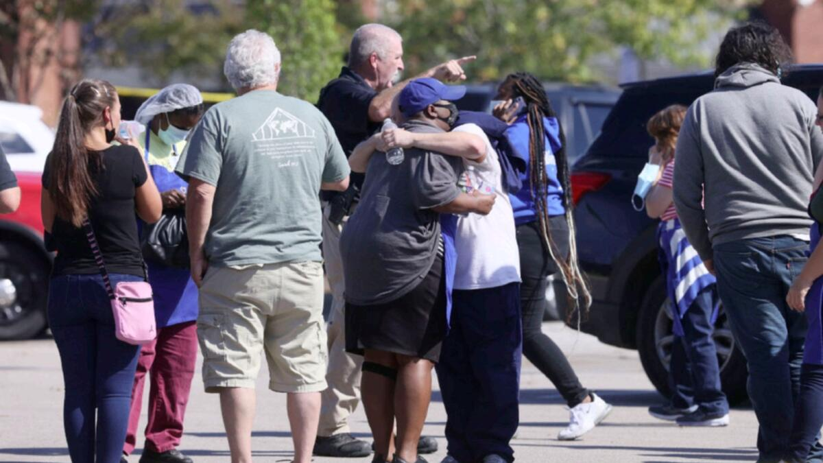 People embrace as police respond to the scene of a shooting at a Kroger's grocery store in Collierville, Tennessee. — AP