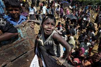 Rohingya refugees react as aid is distributed in Coxs Bazar, Bangladesh