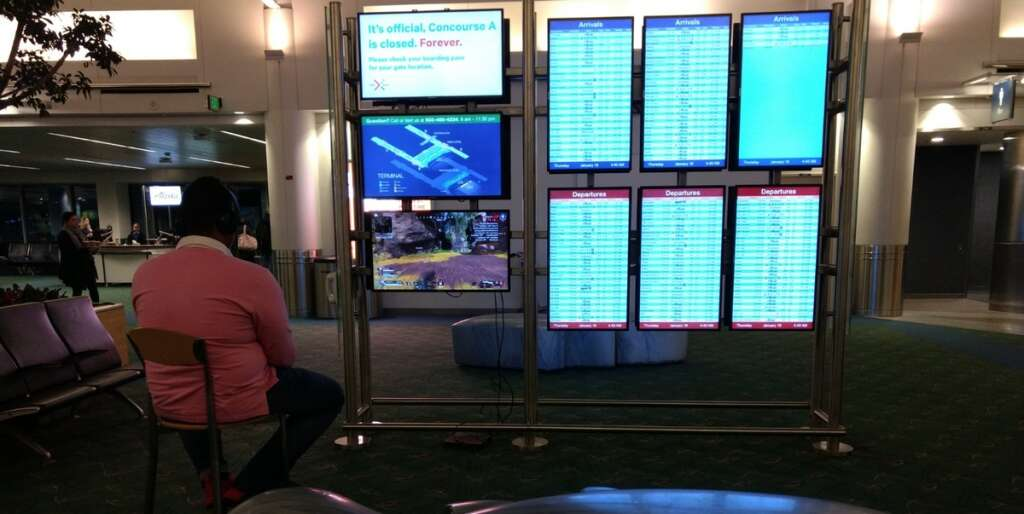 Man uses airport monitor to play video game